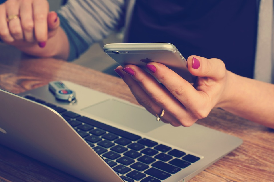 Angestellte mit Notebook und Smartphone