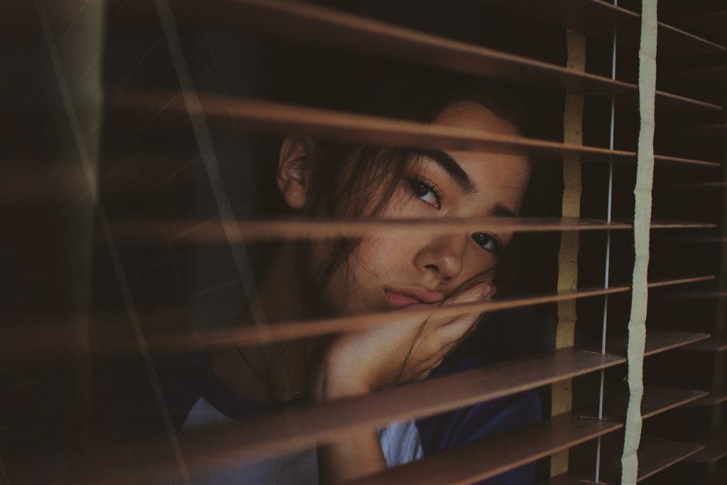Junge Frau schaut traurig aus dem Fenster