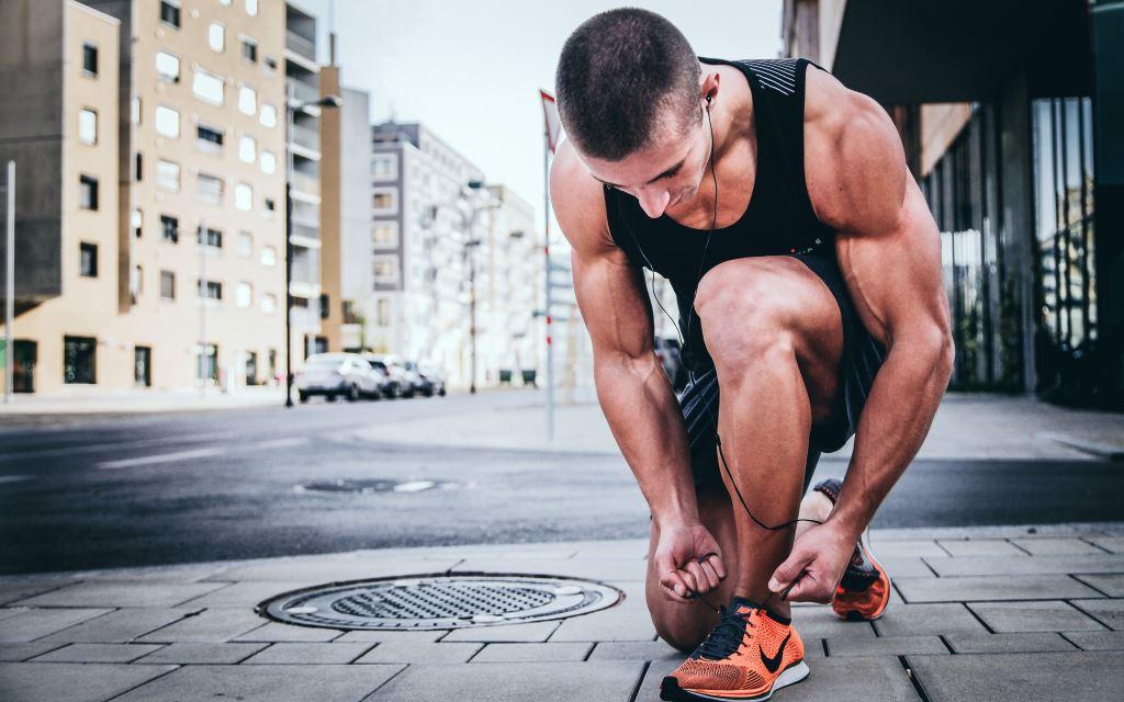 Mann bindet sich Joggenschuhe zum Laufen